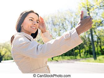 Smiling woman making selfie photo