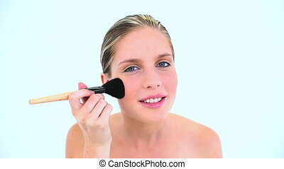 Smiling woman making up her cheek against a white background