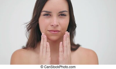 Smiling woman massaging her two cheeks against a white...