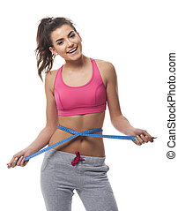 Smiling woman measuring her waist line with tape measure