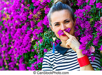smiling woman near colorful magenta flowers bed having fun...
