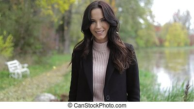 Smiling woman near pond - Pretty woman in black jacket and...