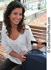 Smiling woman on a bench with luggage