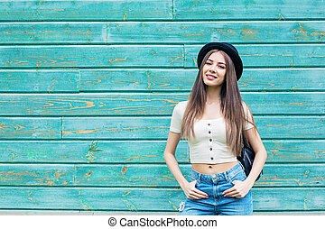 Smiling woman on blue wooden background outdoors