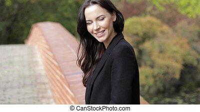 Smiling woman on bridge - Attractive woman in black jacket...