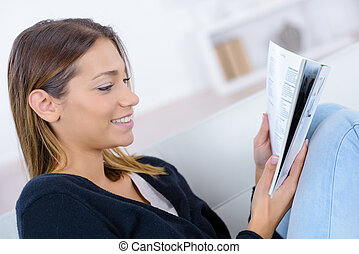 smiling woman on couch reading at home
