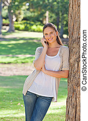 Smiling woman on her cellphone leaning against a tree