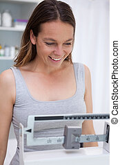 Smiling woman on scale - Smiling woman on medical scale