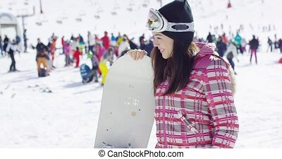 Smiling woman on ski slope with snowboard - Half body...