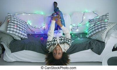 Smiling woman on sofa with twinkle lights - Playful young...