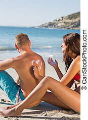 Smiling woman on the beach drawing heart pattern with sun cream on her boyfriends back