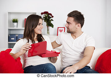 Smiling woman opening a valentine's gift