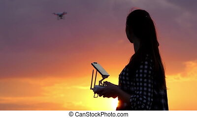 Smiling woman operates a panel to control a drone at sunset