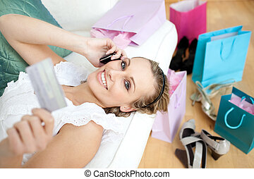 Smiling woman ordering on the phone lying on a sofa