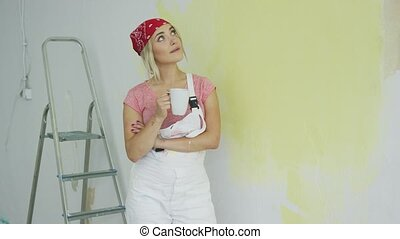 Smiling woman painter standing with drink - Cute young blond...
