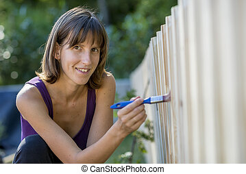Smiling woman painting a garden fence