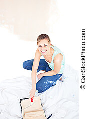 Smiling woman painting a room