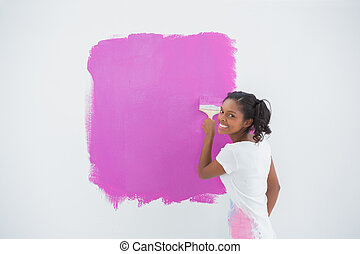 Smiling woman painting her wall in bright pink