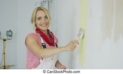 Smiling woman painting wall yellow - Side view of gorgeous...