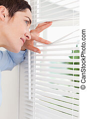Smiling woman peeking out a window