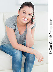 Smiling woman phoning and sitting on the couch