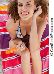 Smiling woman placing her hand near her ear while holding an orange popsicle