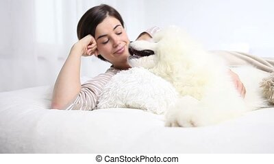 Smiling woman play with pet dog