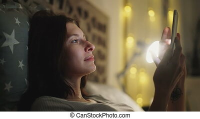 Smiling woman playing online video game on her smartphone lying on bed at home at night