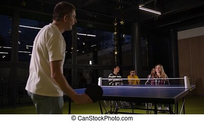 Skillful mature woman in wheelchair rejoicing in success during ping-pong game while playing in pair with disabled man with cerebral palsy. Ppositive emotions, happiness, joy, fun, active lifesyle