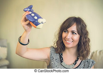 Smiling woman playing with a toy airplane