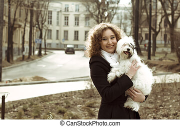 Smiling woman playing with dog  in the street
