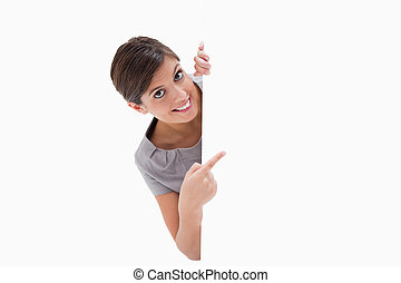 Smiling woman pointing around the corner against a white background