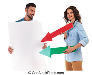 smiling woman pointing arrows to  blank board held by  man
