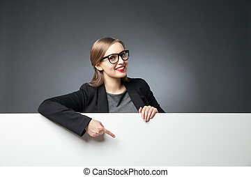Smiling woman pointing at blank space