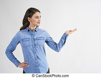 Smiling woman pointing at copy space at studio shot