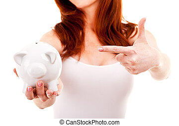 Smiling woman pointing at her piggy bank