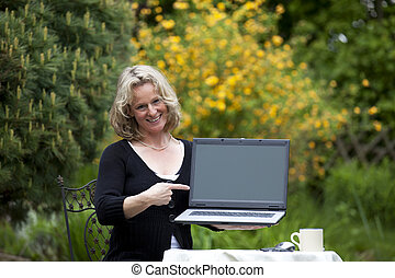 smiling woman pointing at laptop