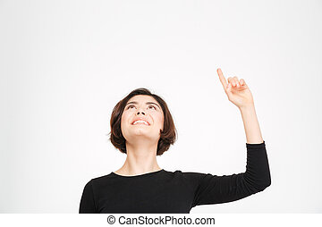 Smiling woman pointing finger up