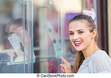 Smiling woman pointing on showcase