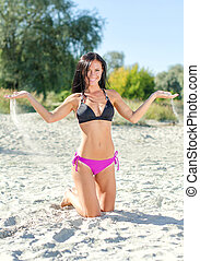 Smiling woman posing on the beach.