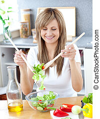 Smiling woman preparing a salad in the kitchen