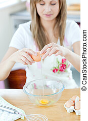 Smiling woman preparing eggs in the kitchen