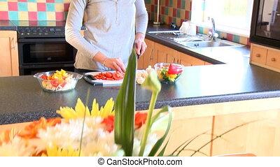 Smiling woman preparing salad