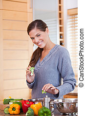 Smiling woman preparing vegetable stew in the kitchen