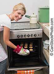 Smiling woman putting a tray of cookies in oven at kitchen