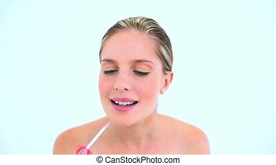 Smiling woman putting lipstick on