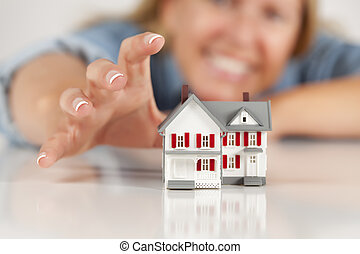 Smiling Woman Reaching for Model House on White - Smiling...