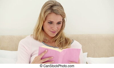 Smiling woman reading a book in her bed