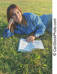 Smiling woman reading a  book in nature