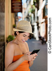 Smiling woman reading a sms on her mobile